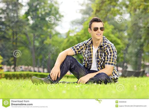 Handsome Guy With Sunglasses Sitting On Grass And Looking